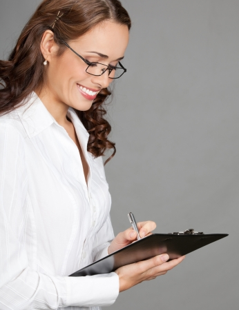 Happy smiling young beautiful business woman with clipboard writing, over gray background photo