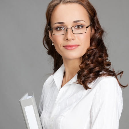 Portrait of happy smiling young business woman with gray folder, over gray background photo