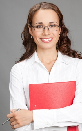 Portrait of happy smiling young business woman with red folder, over gray background Stock Photo - 17391226