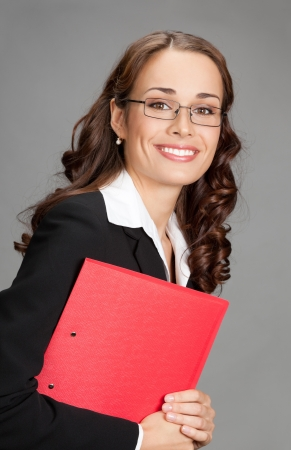 Portrait of happy smiling young business woman with red folder, over gray background photo