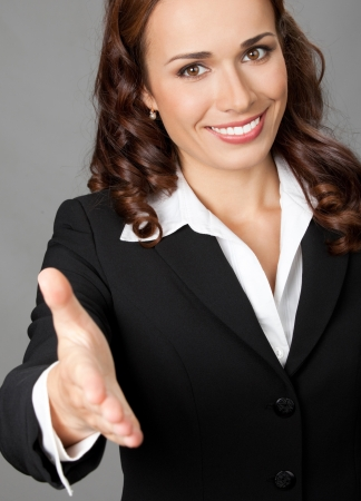 Portrait of young cheerful beautiful business woman giving hand for handshake, over grey background photo