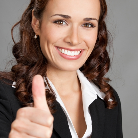 Happy smiling cheerful young business woman showing thumbs up gesture, over grey background Stock Photo - 17391262