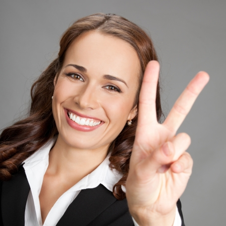 Happy smiling beautiful young business woman showing two fingers or victory gesture, over gray background Stock Photo - 17391254