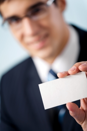 Happy smiling businessman showing blank business card, at office. Focus on hand. Stock Photo - 17416102