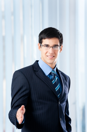 Happy smiling young business man giving hand for handshake, at office, with copyspace photo