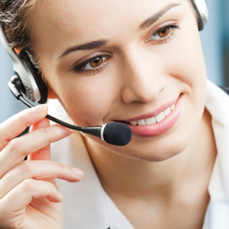 headset help: Portrait of happy smiling cheerful support phone operator in headset at office
