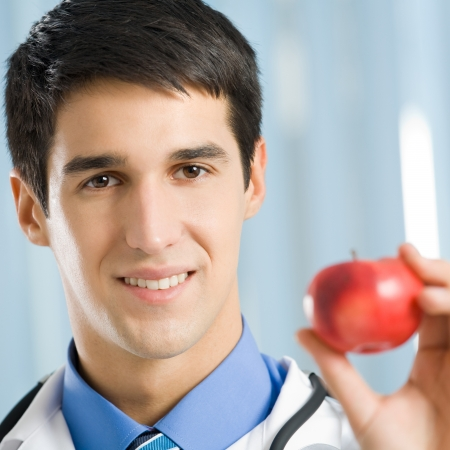 Portrait of happy smiling cheerful young doctor with apple, at office photo