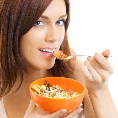 Enthousiaste belle femme manger mousseline, isolé sur fond blanc