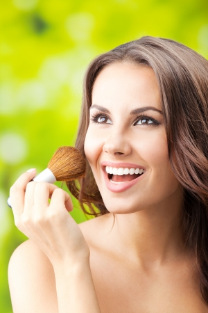 Portrait of young happy smiling woman with make up brush, outdoor photo