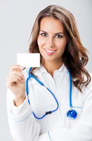 Portrait de sourire heureux jeune femme médecin montrant carte de visite vierge ou une invitation, sur fond gris Banque d'images