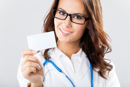 Portrait of happy smiling young female doctor showing blank business card or invitation, over grey background Stock Photo - 17768046