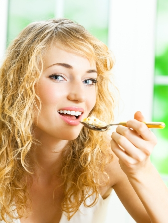 muslin: Cheerful blond woman eating cereal muslin  Stock Photo