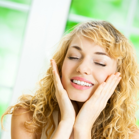 woman face cream: Portrait of young happy smiling cheerful beautiful blond woman applying creme, at home Stock Photo