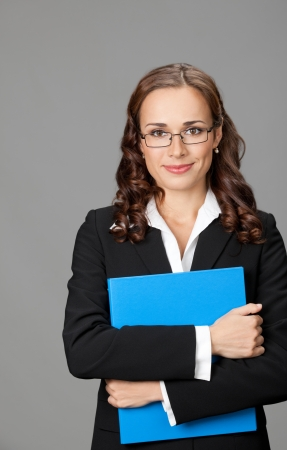 Portrait of happy smiling young business woman with blue folder, over gray background photo