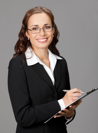 Portrait of happy smiling business woman with clipboard, over gray background photo