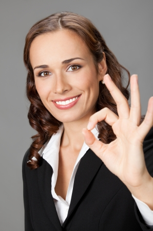Happy smiling beautiful young business woman showing okay gesture, over gray background Stock Photo - 17768045