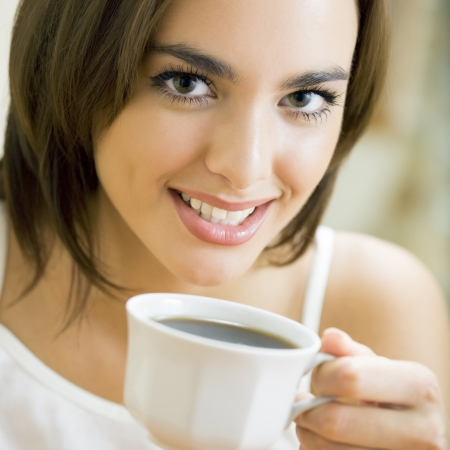 people drinking coffee: Young happy smiling woman drinking coffee, at home
