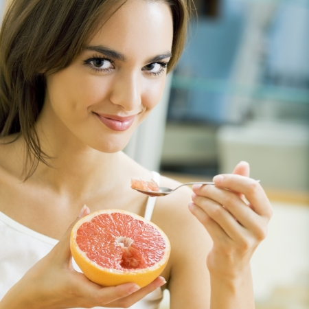 portarit: Portarit of young woman eating grapefruit at home Stock Photo