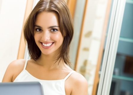 Cheerfull smiling woman working with laptop, at home Stock Photo - 17888293
