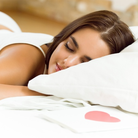 1 young woman only: Young sleeping woman with valentine card on bed