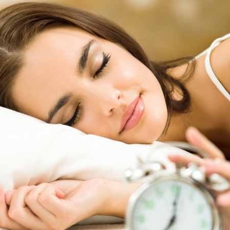 woman with clock: Young woman with alarmclock on the bed at the morning