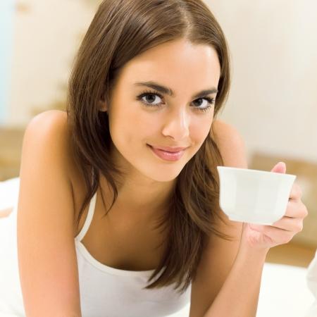 donna che beve il caff�: Giovane sorridente felice donna bere caff?, a casa Archivio Fotografico