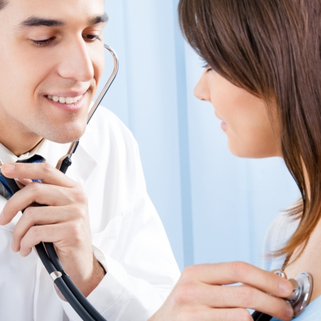 Doctor examing female patient with stethoscope in hospital Stock Photo - 17888250