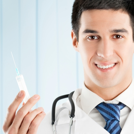 Portrait of cheerful doctor with syringe photo