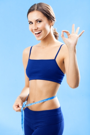 Cheerful woman in fitness wear with tape, showing okay gesture, over blue background