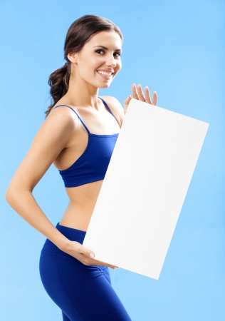 blank area: Cheerful young woman in fitness wear showing blank signboard or copyspace, over blue background Stock Photo