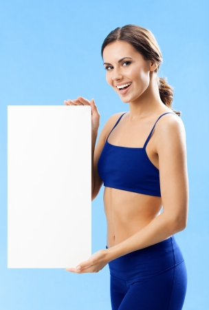 Cheerful young woman in fitness wear showing blank signboard or copyspace, over blue background photo