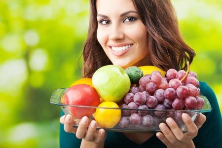 european food: Joven mujer feliz sonriendo con plato de frutas, al aire libre,