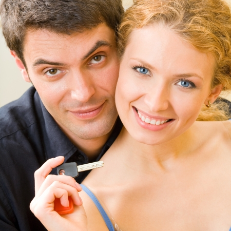 homebuyer: Cheerful couple or young family showing key of new car or flat