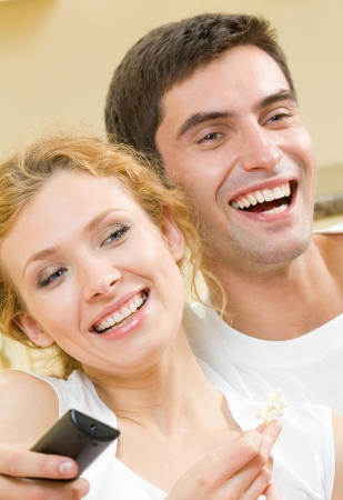 Cheerful young couple watching TV together photo