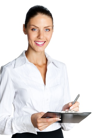 Cheerful beautiful business woman with clipboard writing, isolated over white background photo