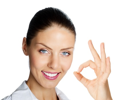 Cheerful beautiful young business woman showing okay gesture, isolated over white background