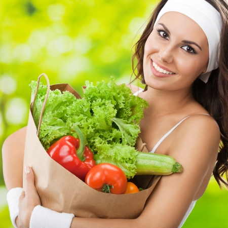 individual sport: Portrait of happy smiling young beautiful woman in fitness wear holding grocery shopping bag with healthy vegetarian food, outdoors