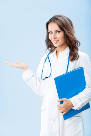 Portrait of young female doctor showing something or copyspase for product or sign text, with blue foder, over blue background photo