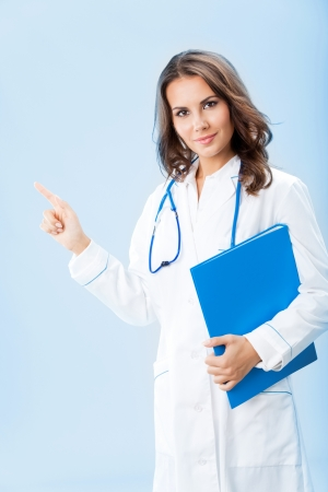 Portrait of young female doctor showing something or copyspase for product or sign text, with blue foder, over blue background Stock Photo - 18204938