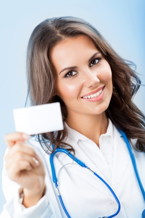 Portrait of happy smiling young female doctor showing blank business card or invitation, over blue background photo