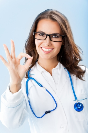 Happy smiling young female doctor showing okay gesture, over blue background Stock Photo - 18204934