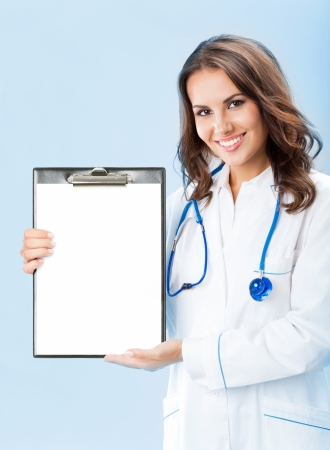 Happy smiling young female doctor showing okay gesture, over blue background photo