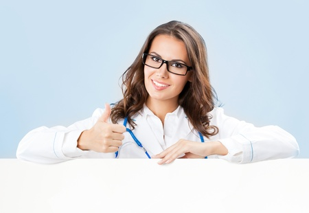 Portrait of happy smiling young female doctor showing blank signboard, over blue background Stock Photo - 18204734