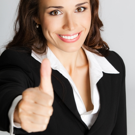 Happy smiling business woman showing thumbs up gesture, over gray background Stock Photo - 18204728