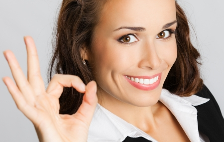 Happy smiling cheerful young business woman with okay gesture, over gray background Stock Photo - 18204684