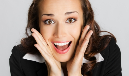 Portrait of young happy smiling surprised business woman, over gray background photo