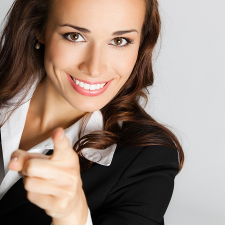 looking forward: Portrait of young smiling business woman pointing finger at viewer, over gray background