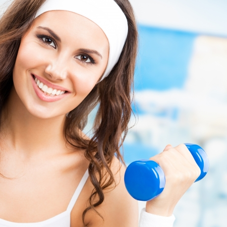 Cheerful woman in fitness wear exercising with dumbbell, at fitness center or gym photo