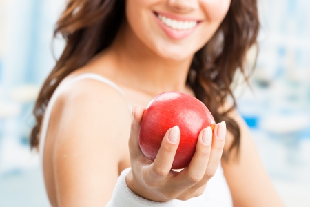 Cheerful woman with red apple, at fitness center or gym, selective focus on hand. photo