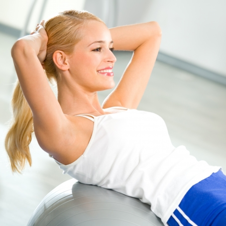 sports wear: Young happy woman doing fitness exercises with fit ball at home